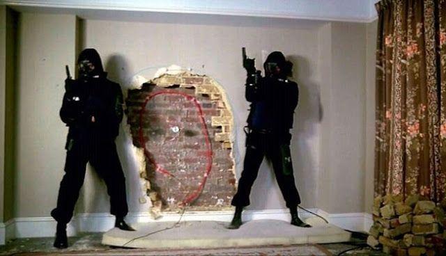 Two SAS men in black counter-terrorist uniforms about to blast through a wall