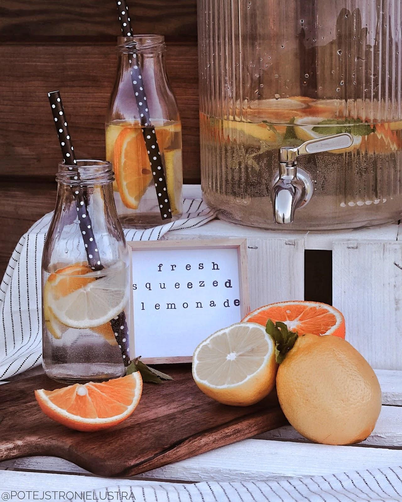 stand z lemoniadą na imprezie w ogrodzie, słoik z kranikiem, butelki ze słomkami