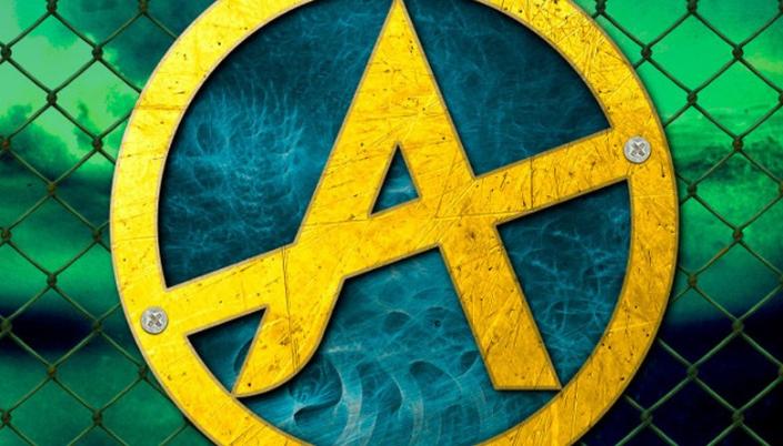 Imagem: uma logo metálica em azul e amarelo de uma letra A, parafusada em uma grade metálica com um céu de fundo verde e nublado, como que dando a impressão de ser radioativo no fundo.
