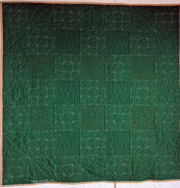 The forest green back highlights the many free motion point-to-point quilting designs