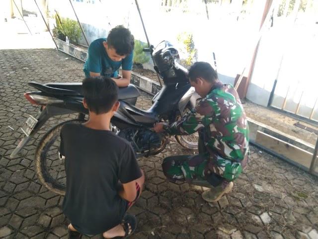 Anggota satgas TMMD bantu warga ganti busi motor yang rusak