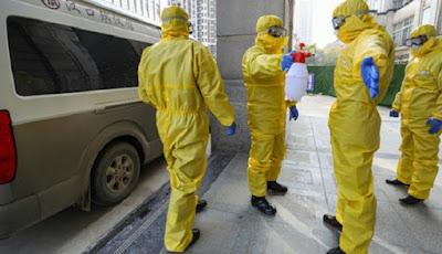 Petugas krematorium menyemprotkan disinfektan