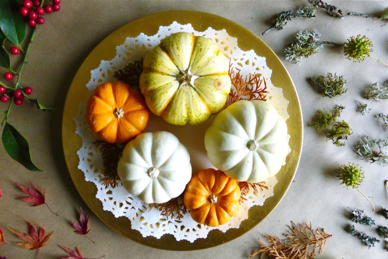 mini pumpkins, gold charger plate, doily, moss, Japanese maple leaves, sweet gum seed pods, holly berries
