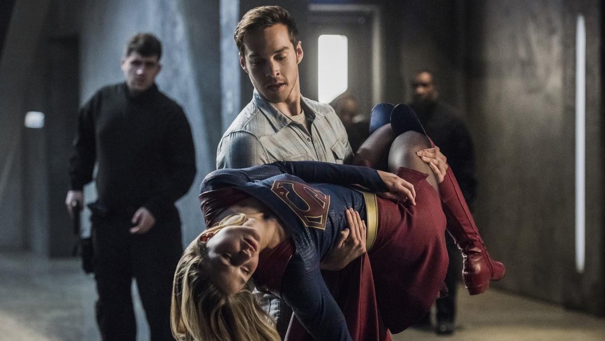 Supergirl en brazos de Mon-El tras ser abatida por Music Meister, interpretado por Darren Criss