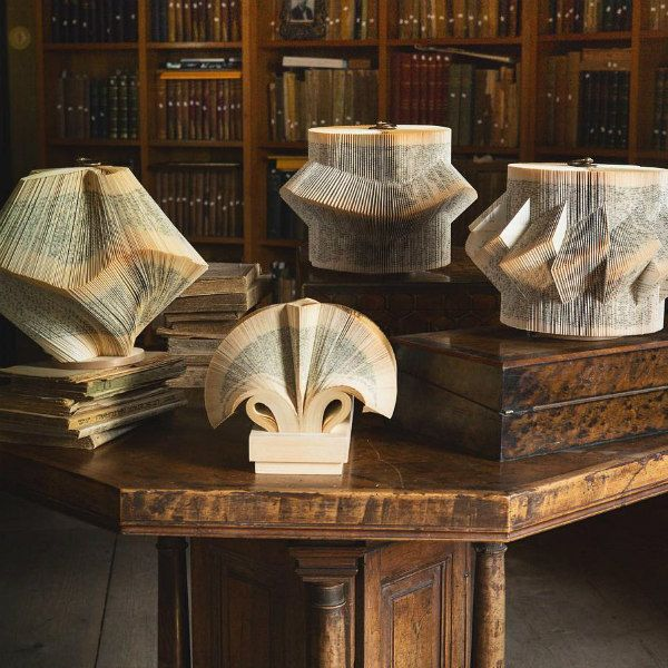 four folded book sculptures arranged on table in library