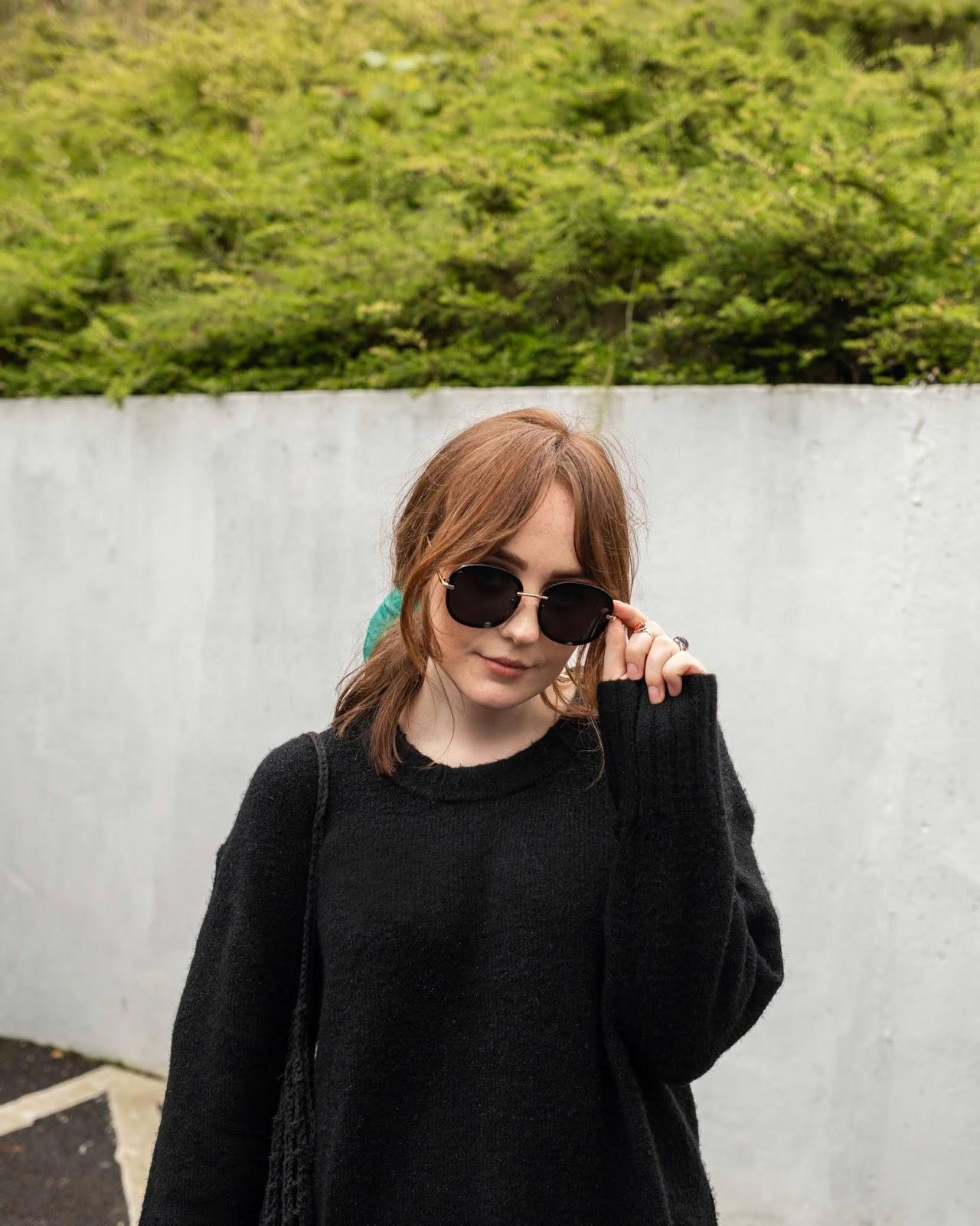 blogger wearing black sunglasses and oversized black jumper