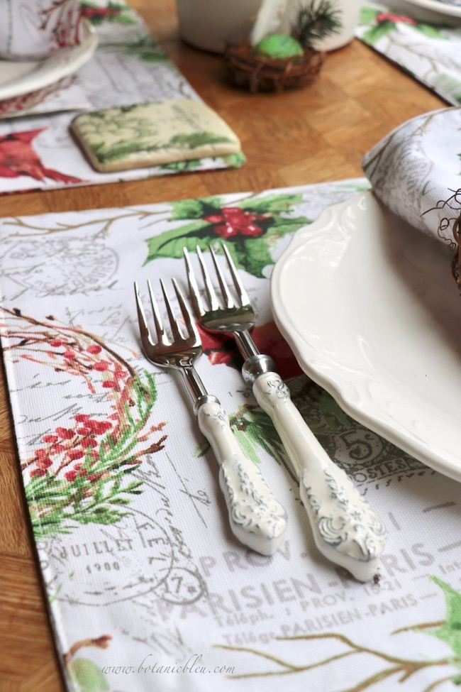 Cardinal Christmas Table Setting linens have French script backgrounds