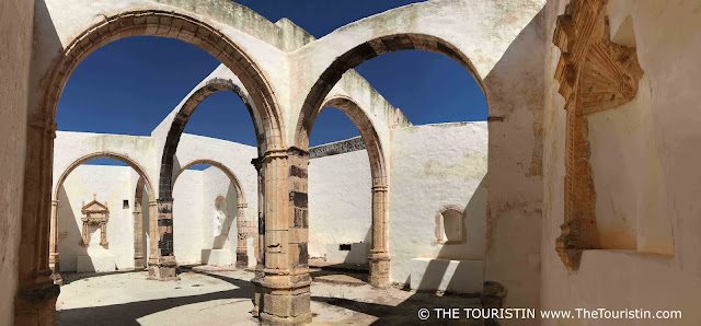 Six archways of an abandoned monastery under a blue sky