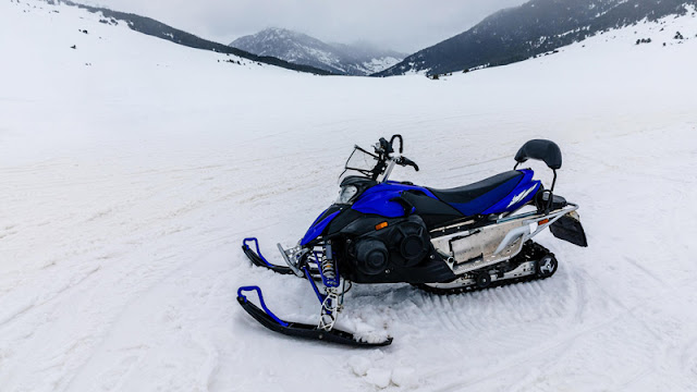 a blue snowmobile poised to head down a snowy canyon
