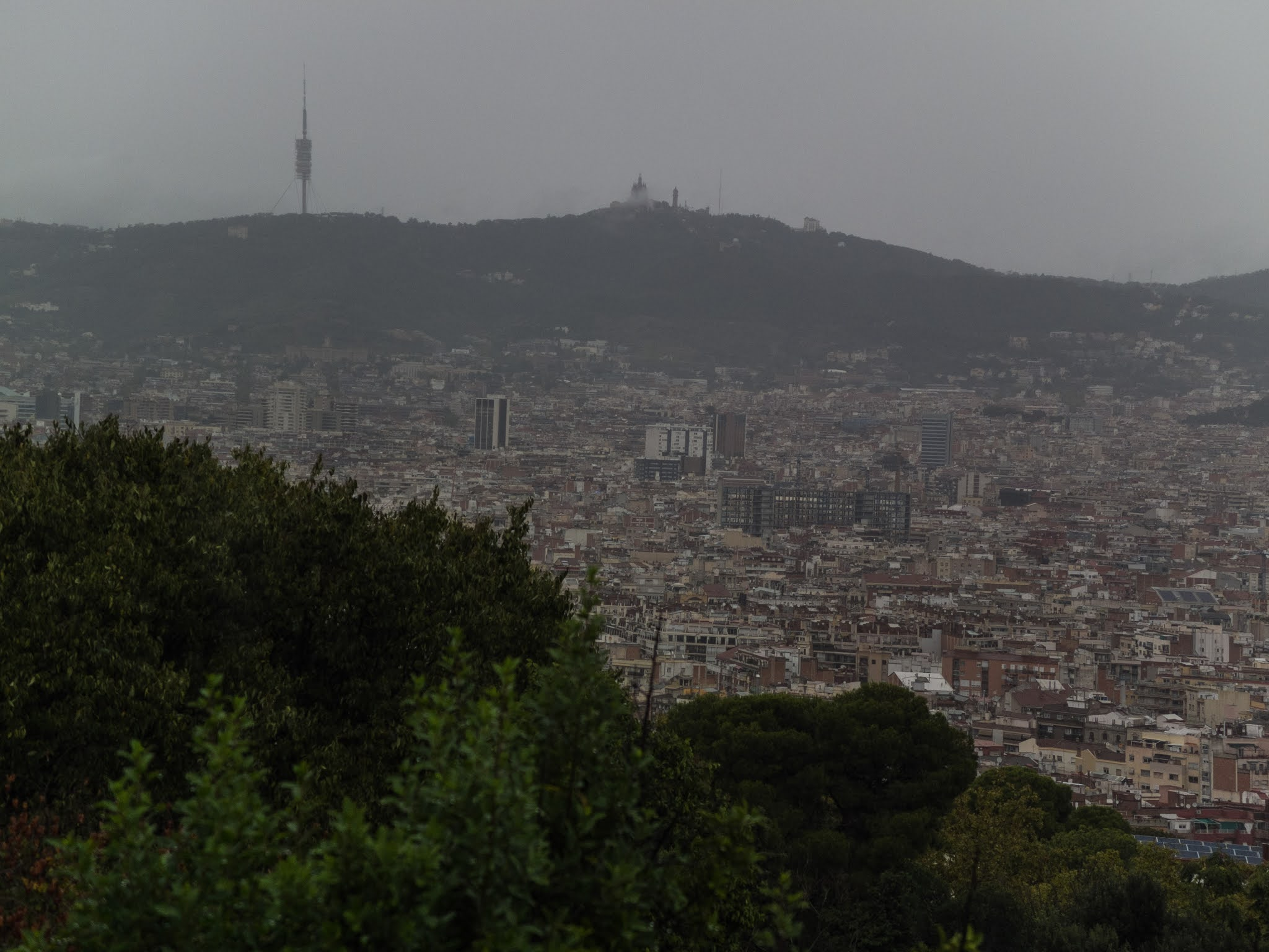 View of the city of Barcelona on a rainy day with mountains in the background.
