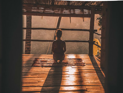 image of woman meditating on floor with overlooking trees