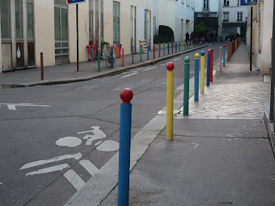 Paris street Allee Verte; buildings across the street, a line of colorful, slender bollards running down this side.
