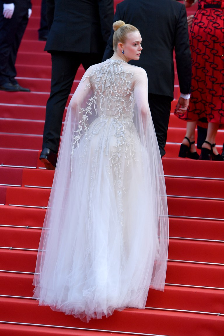 Elle is wearing a Reem Acra dress
