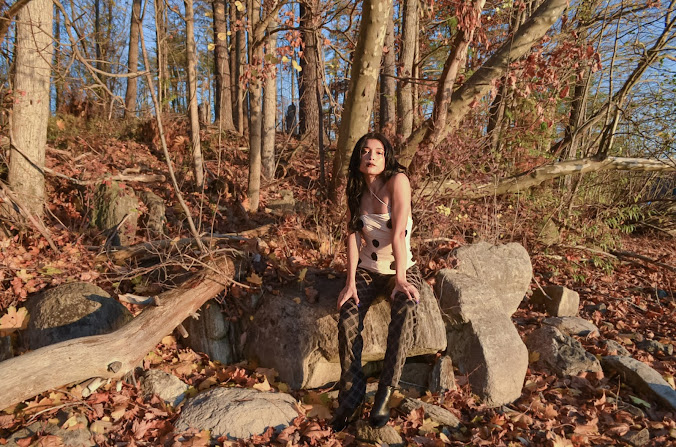 Sitting on a rock , cool pose, Versace logo pants, brown beige medusa logo, Jacquemus polka dot top strapple top, beige top with black dots, trees and leaves and a lake in the background, fall mood, North Salem, NY 2020