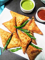 Serving samosa with fried green chili, sweet chutney and green chutney in background