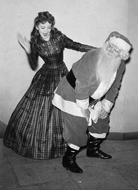 Actress Ida Lupino in period costume spanks a bad Santa. c.1940s.A Pleasant Christmas Story and other stories of Christmas Creepers. marchmatron.com.