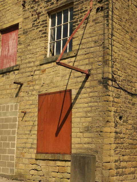 Windows, bricked up windows and remains of metal sign on old brick building at Sowerby Bridge