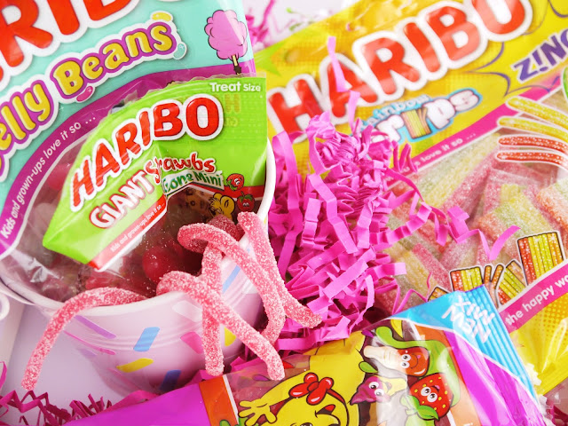 bags of strawberry sweets and jelly beans sat in a small pink metal bucket, with a yellow bag of rainbow strip sweets beside it