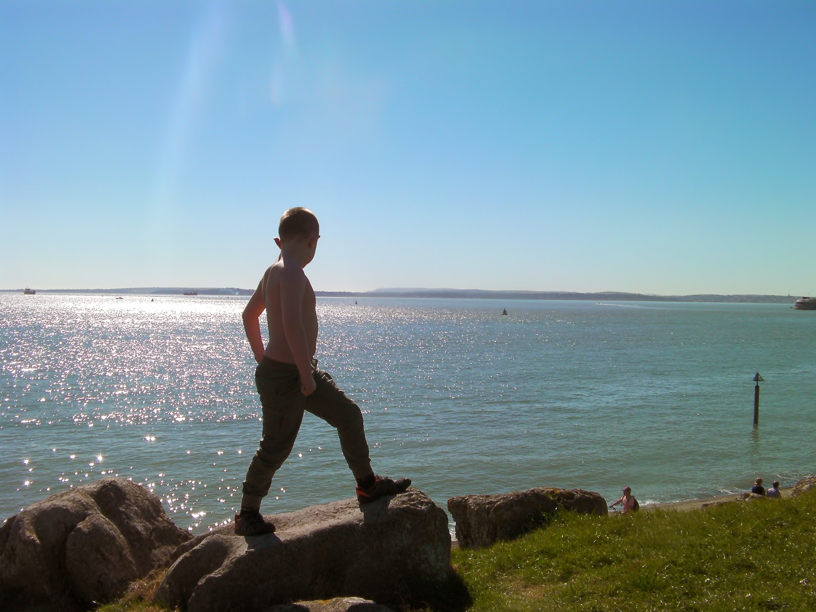 shirtless boy admires calm sea view and cloudless sky
