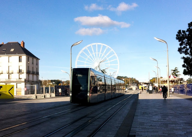 Tram on Rue Nationale in Tours with backdrop of ferris wheel and blue sky