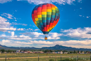 Cramer Imaging's fine art photograph of a hot air balloon taking flight in Panguitch Utah over a farm field and mountains