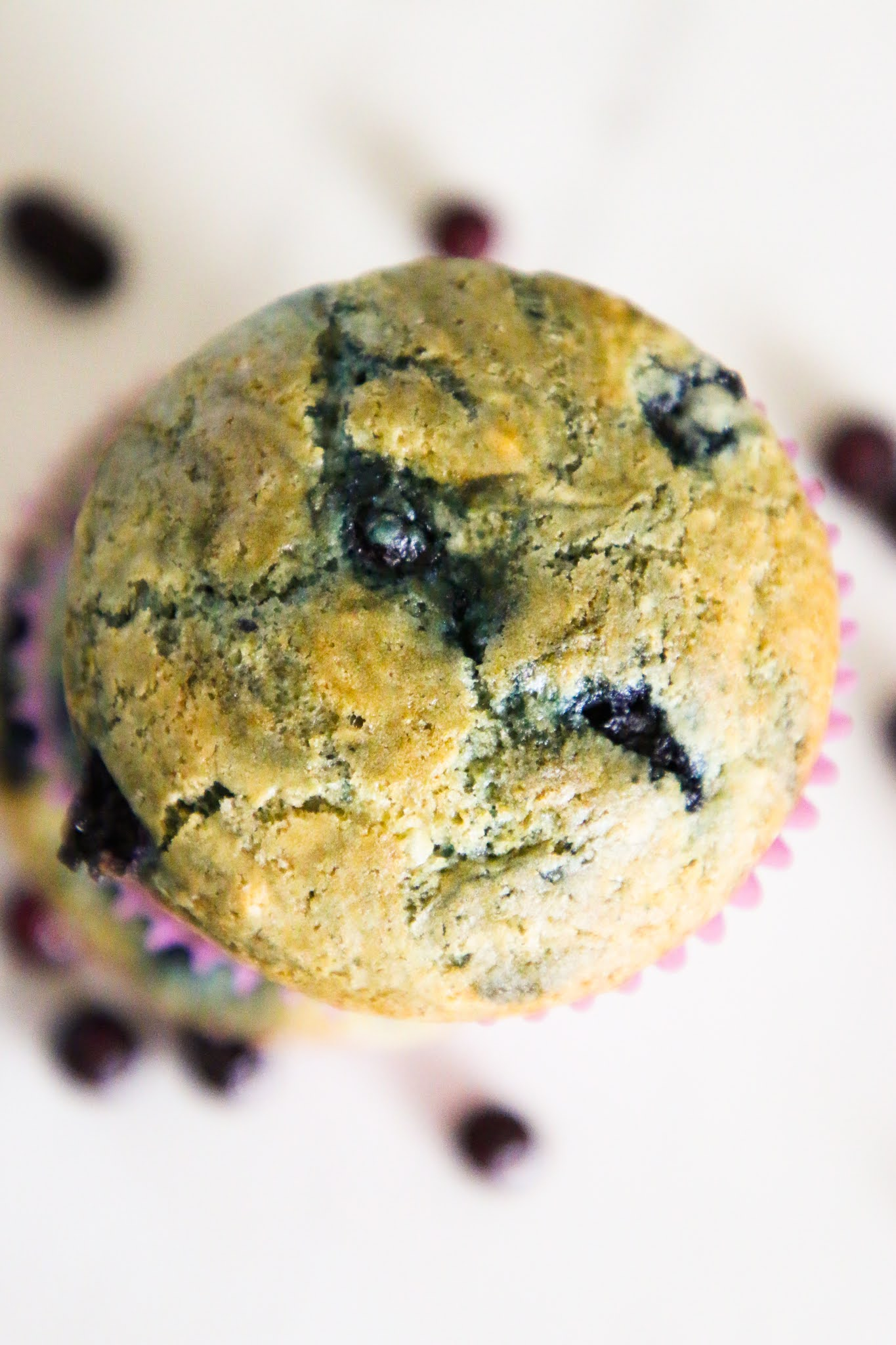 The top of a blueberry muffin on a marble table with scattered blueberries in the background.