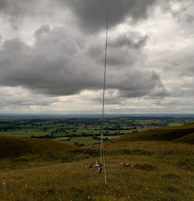The aerial in use on a hilltop. It is mounted on a short wooden post and supported with three guy ropes.