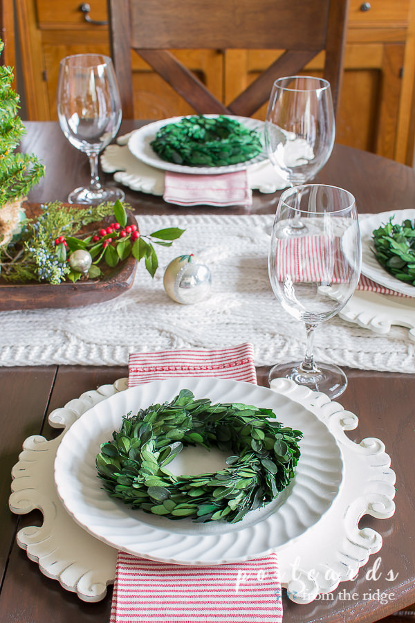 table set with white dishes, red and white striped napkins, and little preserved boxwood wreaths