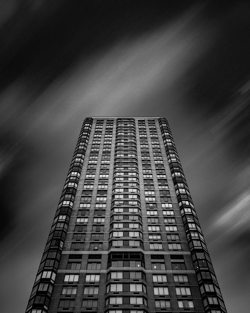 a black and white photograph of a new york building with impressionistic skies