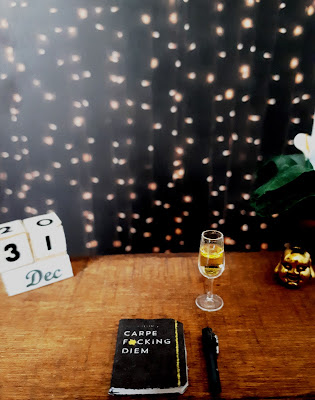 One twelfth scale modern miniature desk with a block calendar showing 31 Dec, a 2020 planner and fountain pen, a glass of sparking wine and a peace lily and laughing buddha head ornament