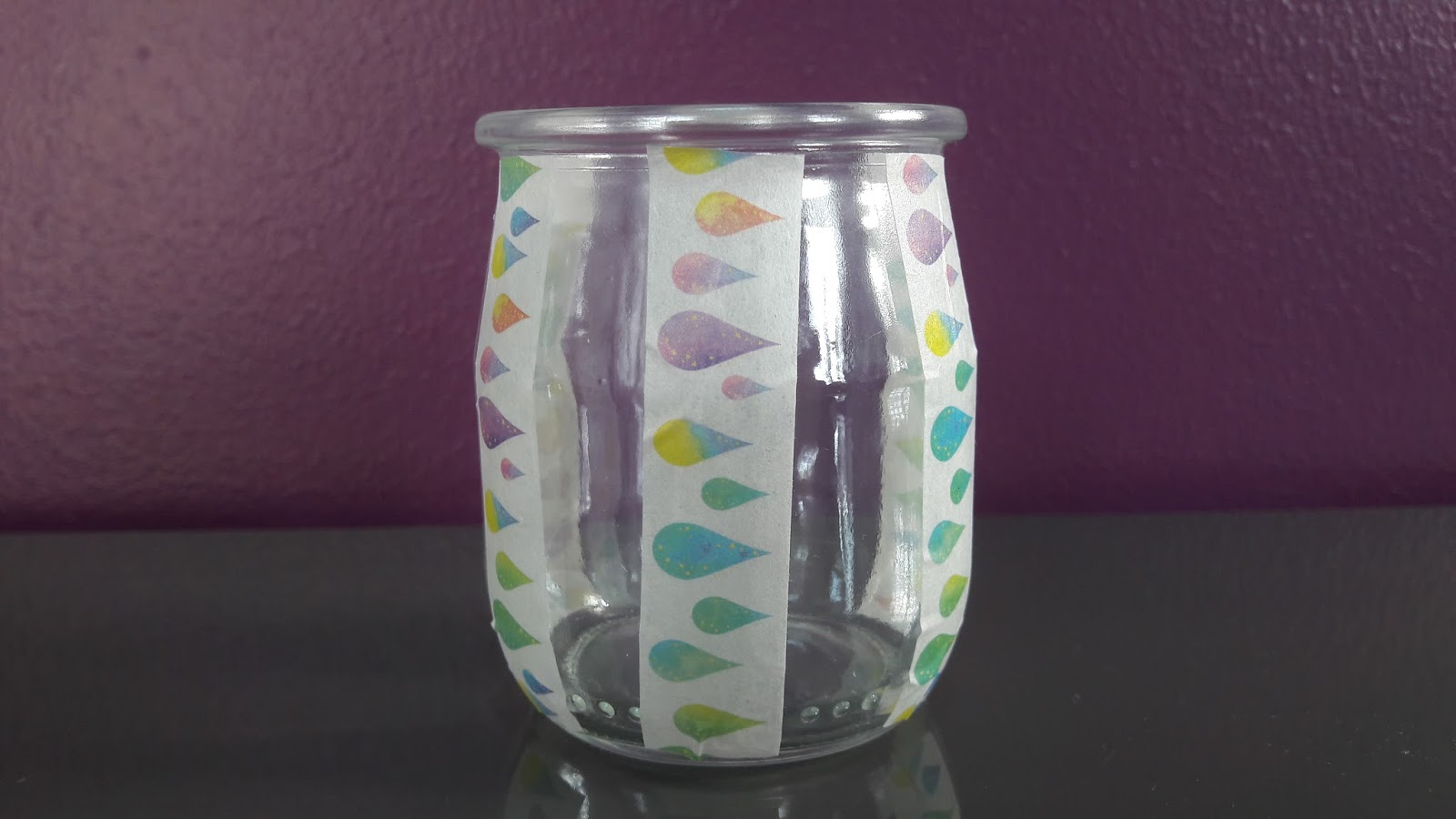 Nous customisons ensuite le pot de yaourt en verre avec un masking tape  gouttes multicolores Pour cela nous appliquons verticalement 6 bandes de la