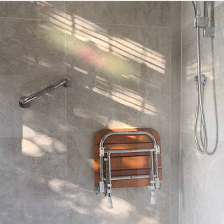 Grey tiled shower with chrome grab rails and a wooden shower chair folded up onto the wall