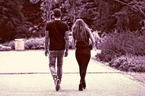 رجل و امرأة يتمشيان في الشارع بين الأشجار الصورة باللون الأبيض والأسود