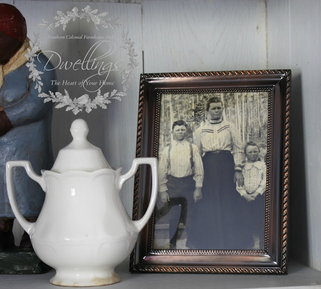 Ironstone and family photos on the farmhouse style cupboard