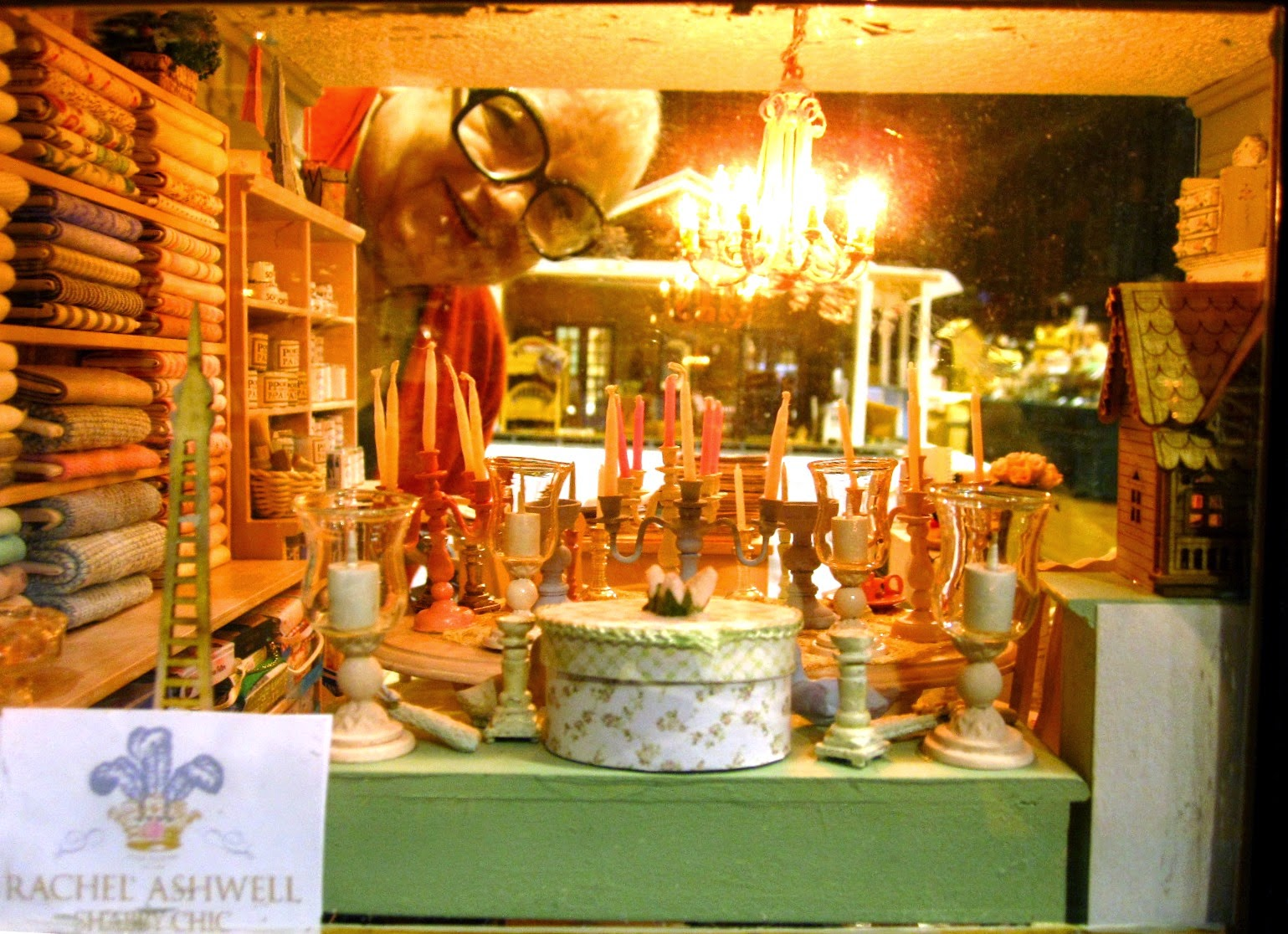 Looking through the front window of a miniature shabby chic shop with the owner peeking in from the back,
