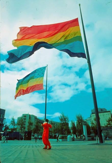 Una persona vestida de rojo está de pie bajo 2 banderas del colores que flotan en el viento.