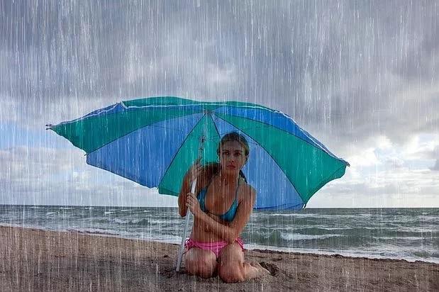 vajzë me çadër në plazh në mot me shi