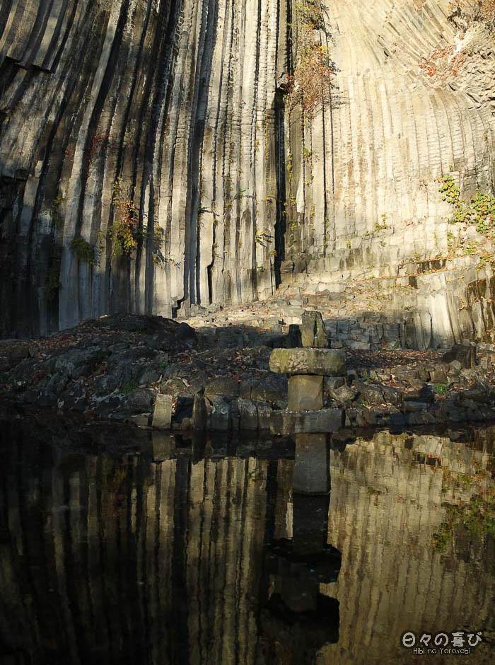 lanterne et colonnes basaltiques se reflètent dans l'eau de l'étang