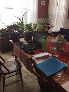 Dining room table with papers and folders strewn next to laptop computer