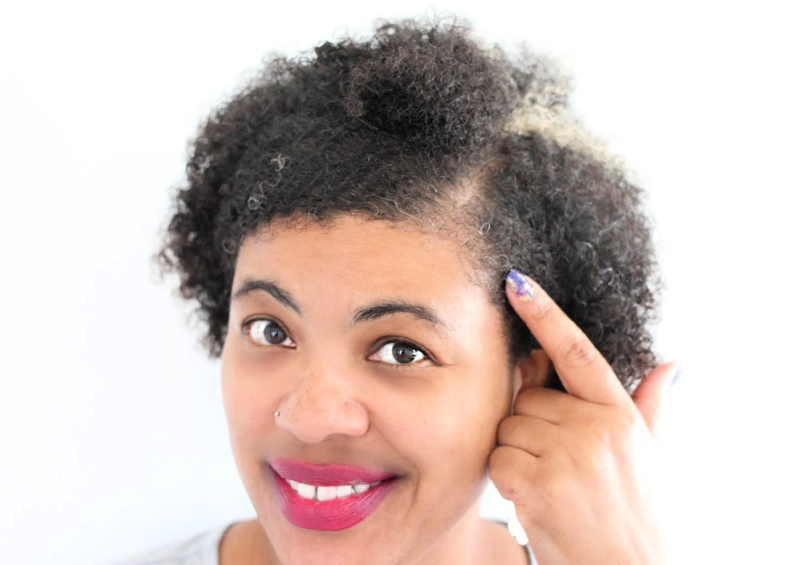 a woman pointing to her gray hairs