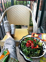 My legs crossed on a balcony chair with a salad on the table next to me.
