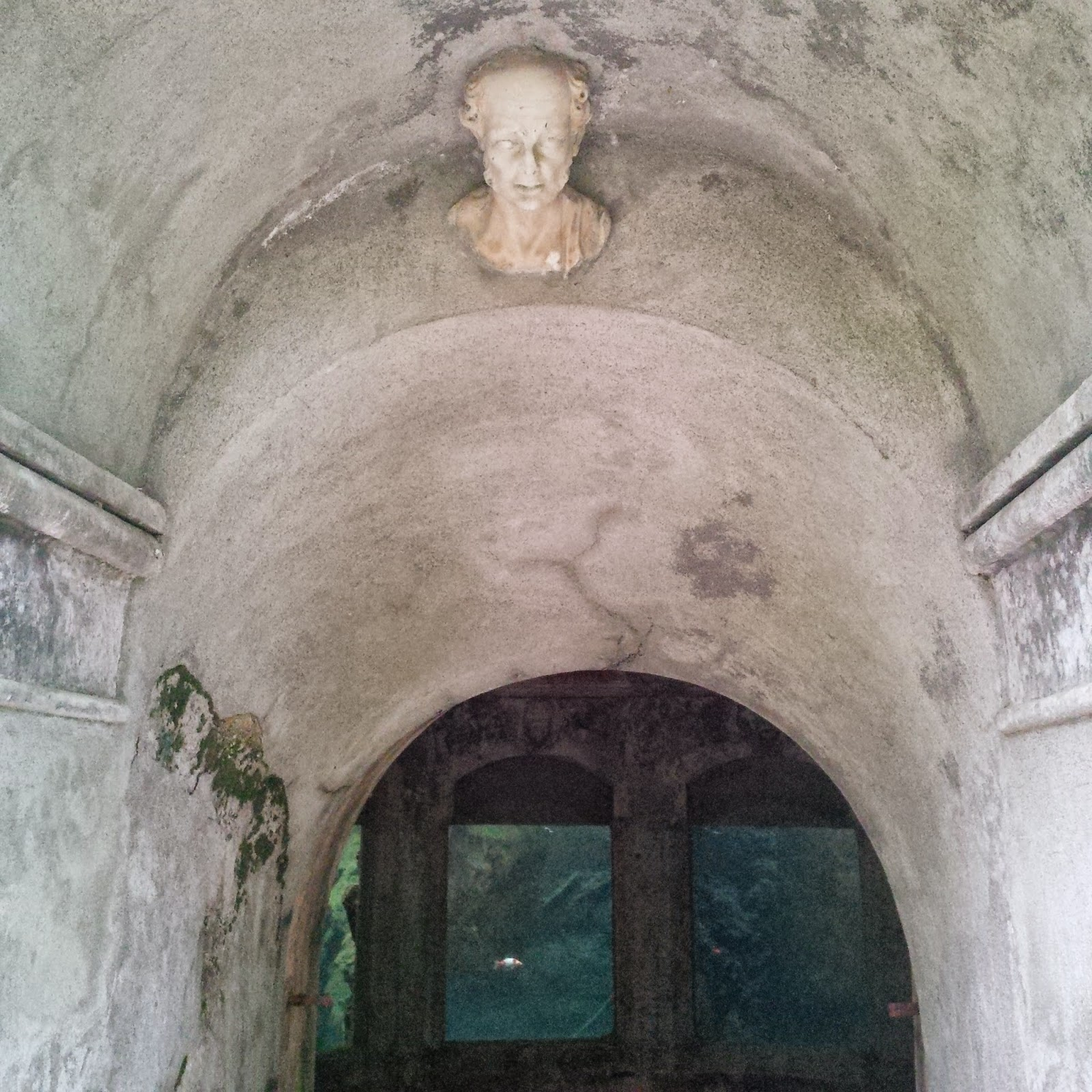A stone face carved above the aquarium in the park of Villa Rossi in Santorso