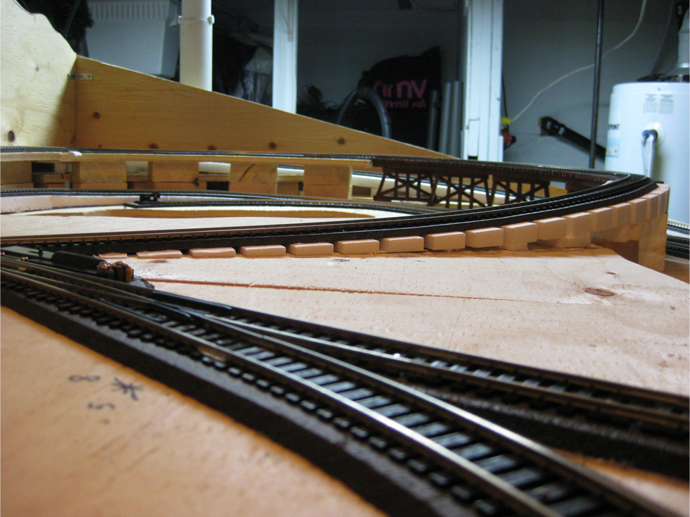 A reduced track grade leading down from a wooden train trestle