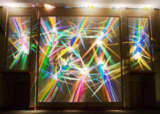 Stephen Knapp's Lightpainting Art shows high polished glass of varing angles to create different colors in his light paintings, shown here with three large frames floating in front of the glass and lights with vivid color spectrums.