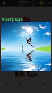 Спортсмен прыгает через реку и преграду в середине на другой берег