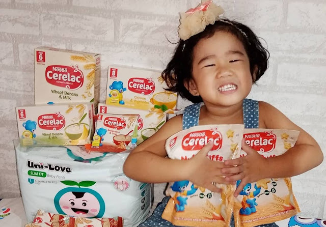 cute baby holding cerelac nutripuffs