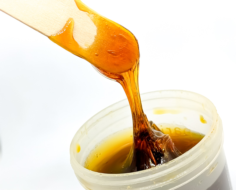 Sugaring vs Waxing - a wooden spatula with sugar wax dripping from it