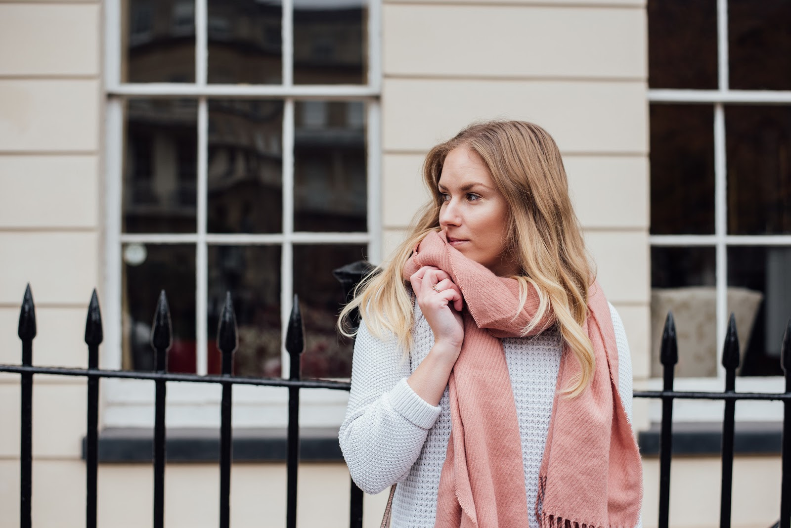 RE wearing a pink scarf, white jumper in front of stone houses