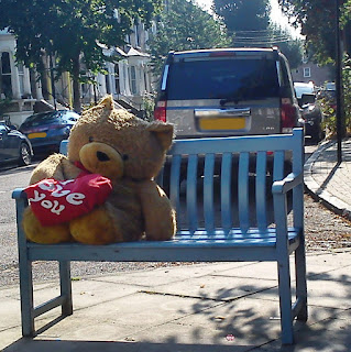 Photo of a large, cute teddy on a blue bench.