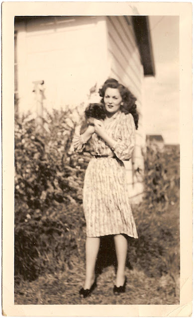 young woman standing outdoors with puppy